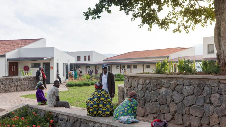 Photo of Butaro District Hospital, Photo by Iwan Baan, Visitors gather on a stone bench near the hospital