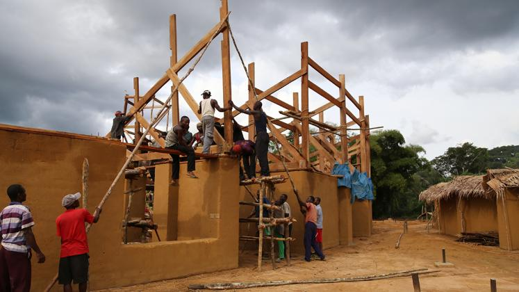 Photo of Ilima Primary School, Community Members hoisting the truss for the school roof