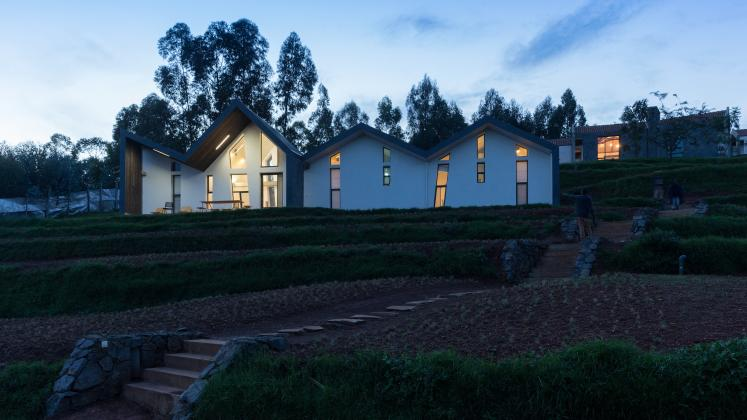 Photo of Butaro Doctors' Sharehousing, Photo by Iwan Baan, Exterior Evening View of the Hill Side and a Housing Unit