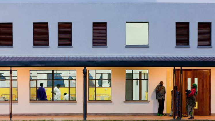 Photo of Butaro District Hospital, Photo by Iwan Baan, Nightitme View of Exterior Hallway with View into Hospital Rooms