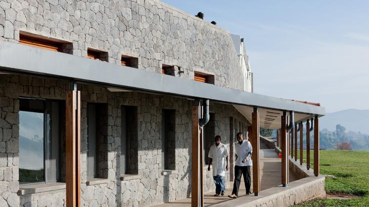 Photo of Butaro District Hospital, Photo by Iwan Baan, Exterior Hallway with Doctor and Patient Passing By