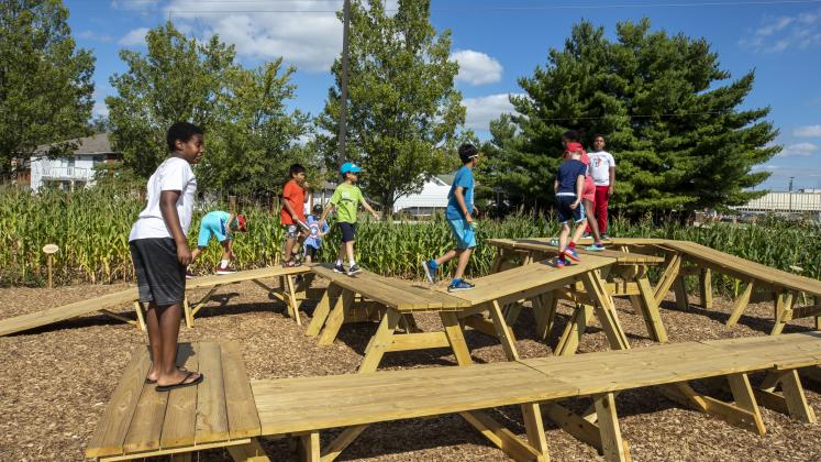 Children from Central Middle School playing on the picnic tables in our Corn / Meal installation