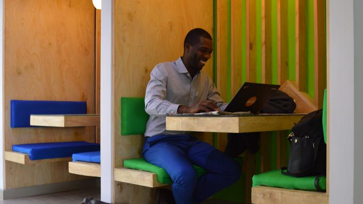 Photo of Young African Leaders Initiative, Christian Benimana working at booth seating