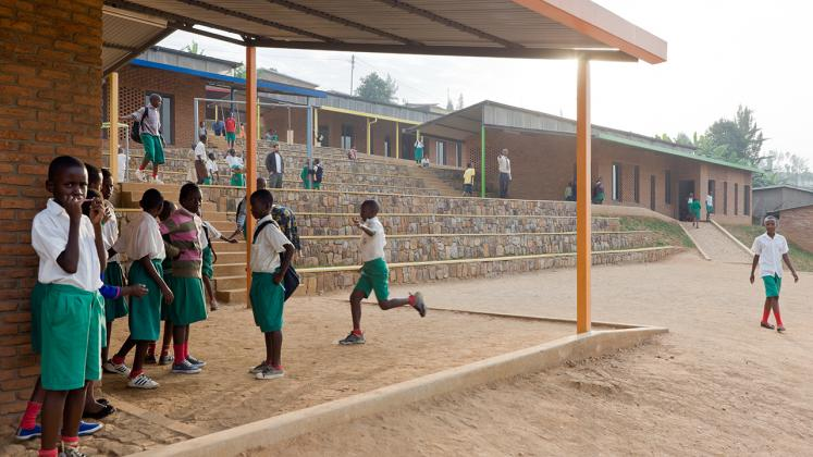 Photo of the Umubano Primary School, Photo by Iwan Baan, View of Tiered Landscape and School Children Playing