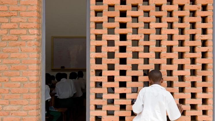 Photo of the Umubkano Primary School, Photo by Iwan Baan, View of Custom Brick Wall with Gaps for Ventilation into Primary School Classroom