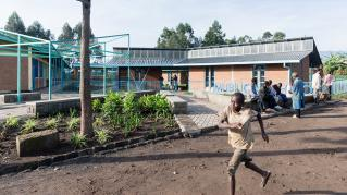 Photo of Mubuga Primary School, Exterior of the school building with children running past